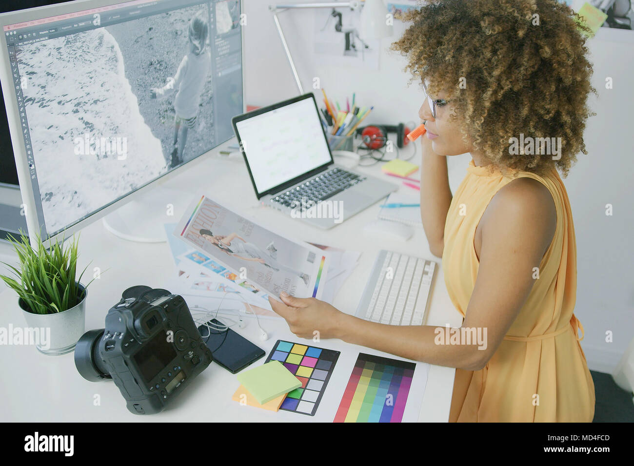 Pensive editor exploring photos - Stock Image