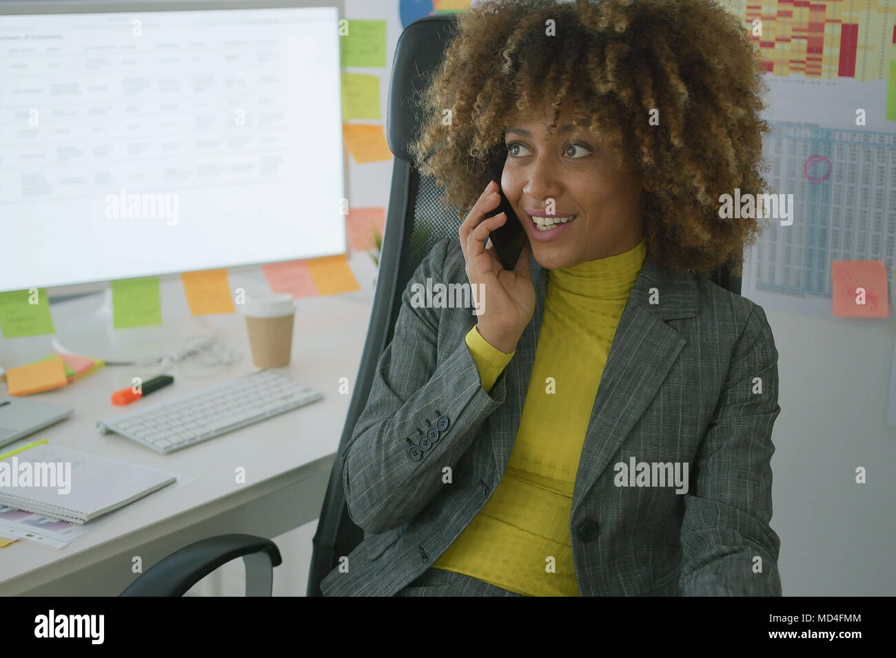 Cheerful elegant worker talking on phone - Stock Image