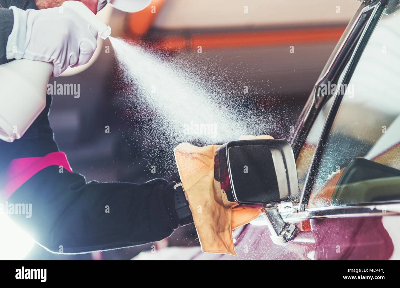 Car Wash Vehicle Detailing. Professional Cleaner Working to Clean Classic Car Body. - Stock Image