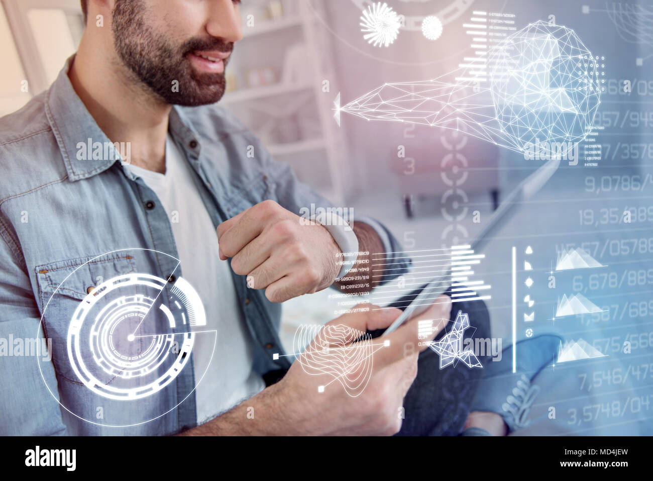 Emotional programmer holding a tablet while testing his smart watch - Stock Image