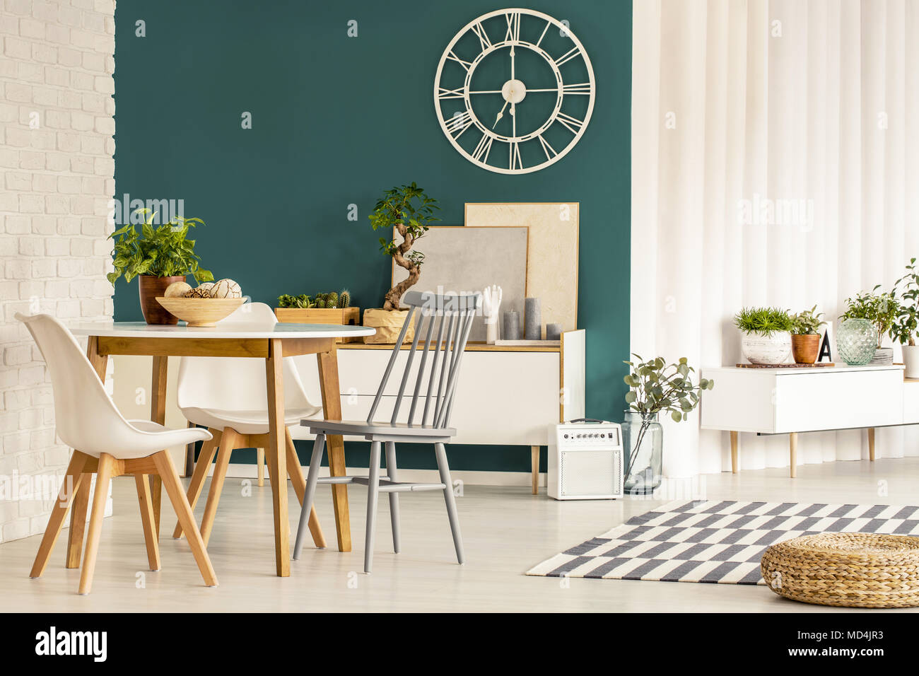 Bright spacious dining room interior with white and gray chairs at a round table and wooden cupboard against green wall & Bright spacious dining room interior with white and gray chairs at ...