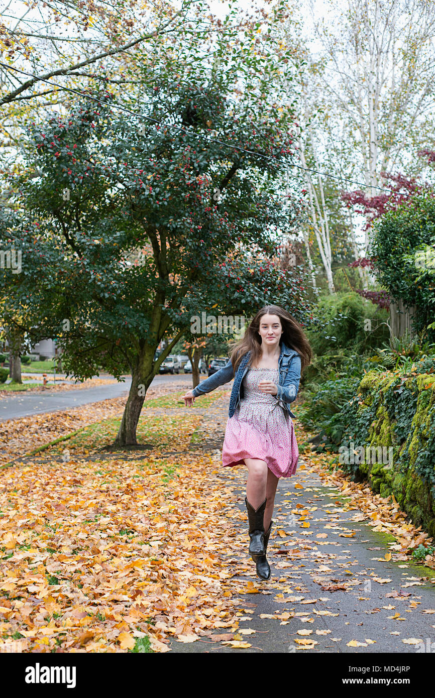 A teenaged girl (13 years old) skipping down the sidewalk. - Stock Image