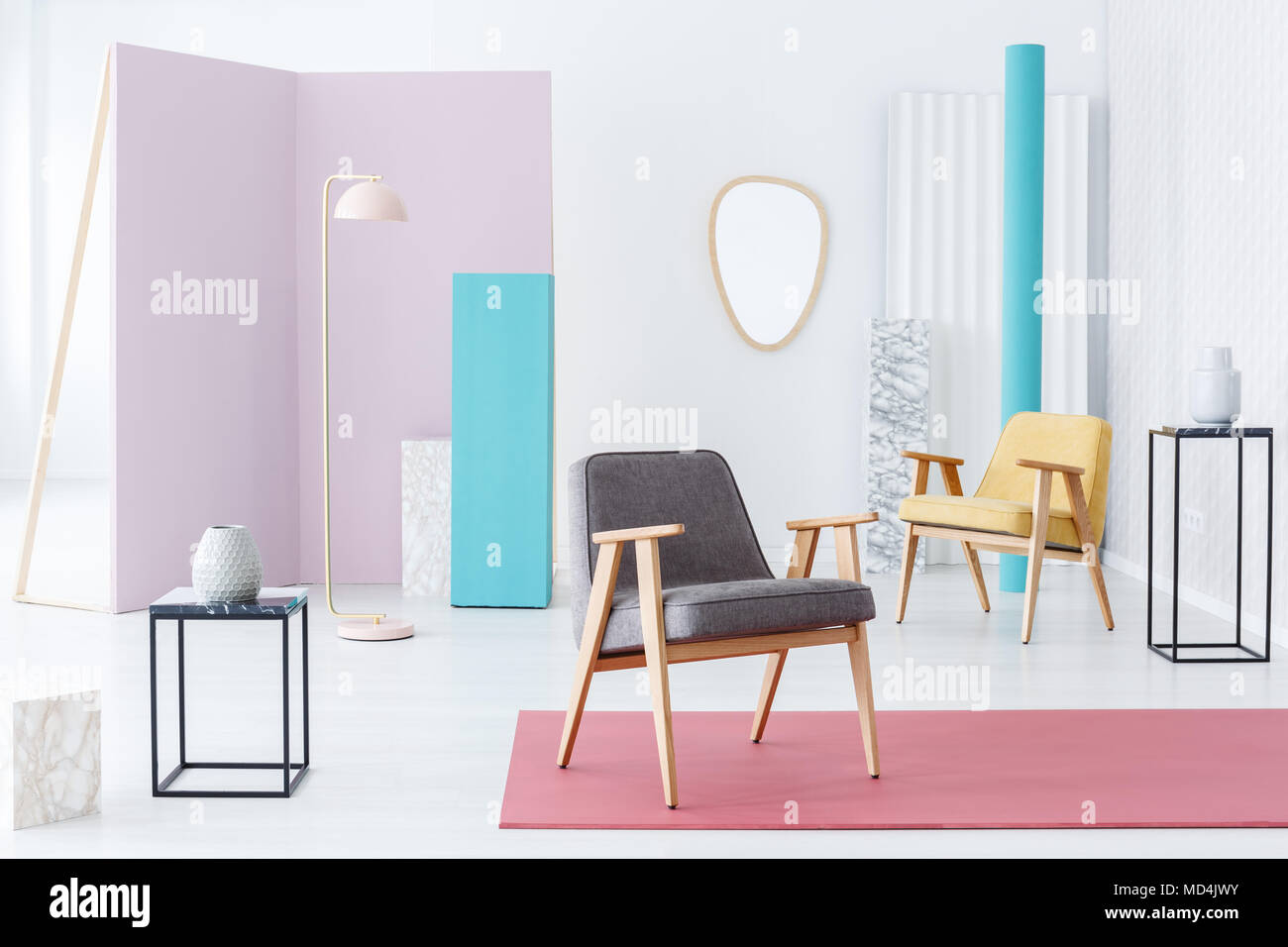 Modern furniture and accessories still life composition in a fun bright interior with pink blue and marble elements and armchairs