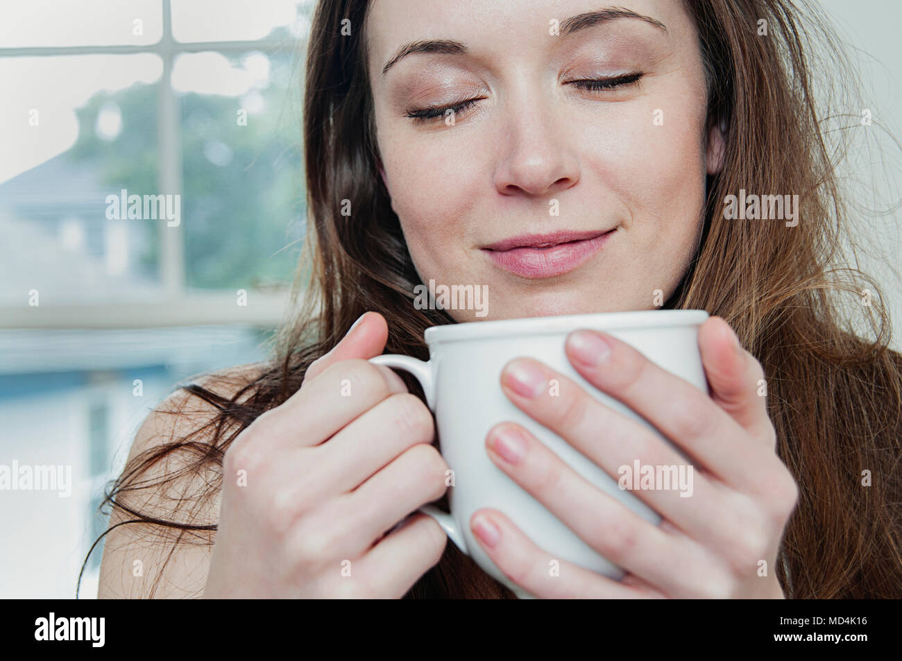 A young woman drinking her morning coffee. - Stock Image
