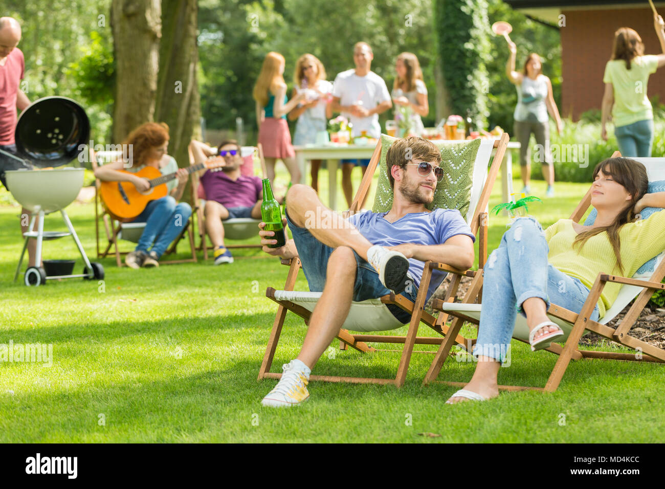 Young friends having barbecue picnic in the nature, playing guitar, playing badminton, enjoying sunny summer day outdoor Stock Photo