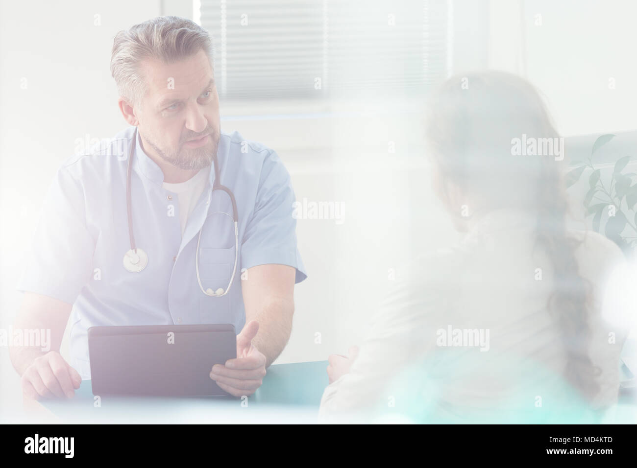 Serious doctor discussing a disease with his patient in hospital Stock Photo