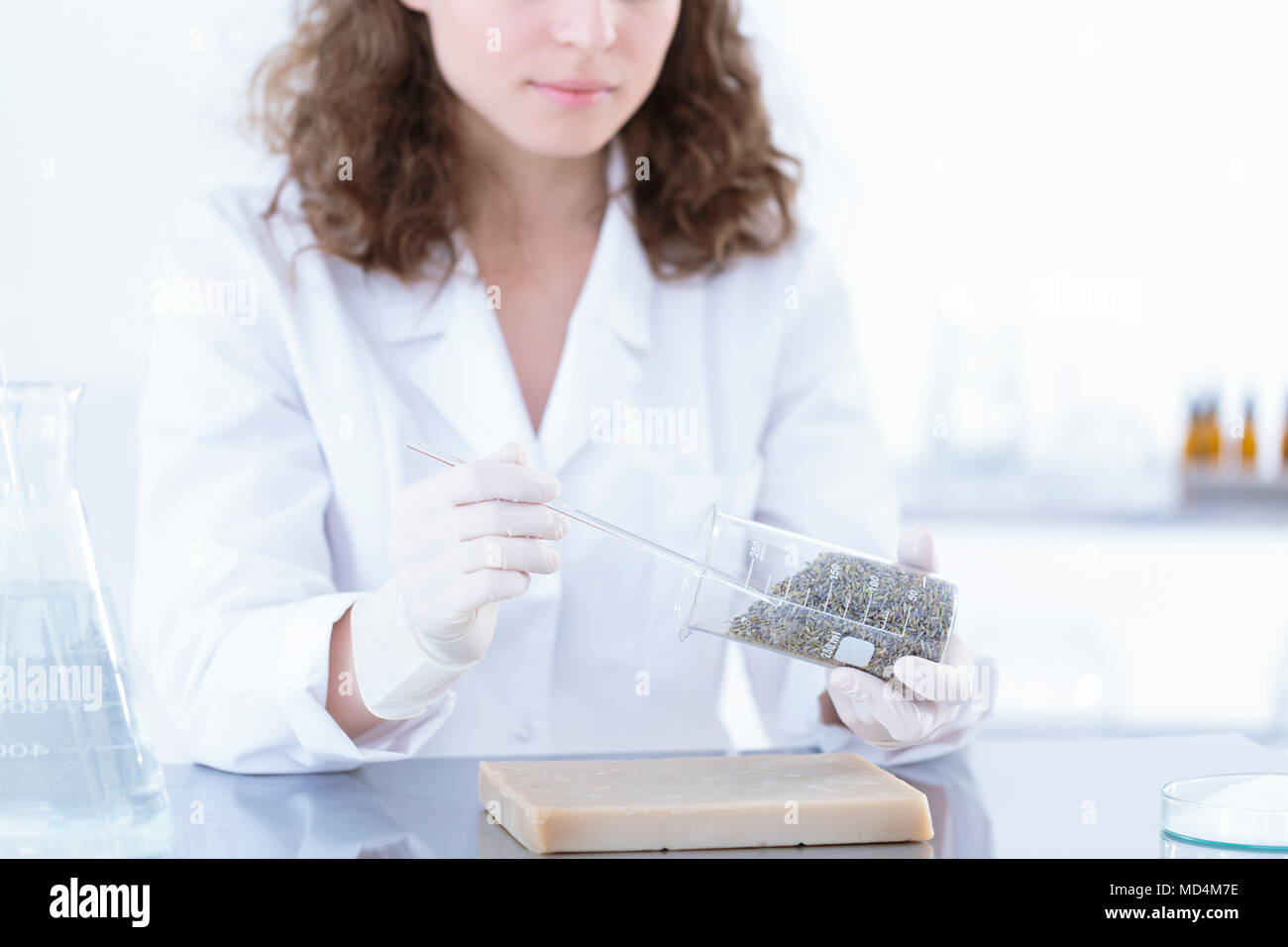 Chemist in white uniform testing herbs during a laboratory analysis - Stock Image