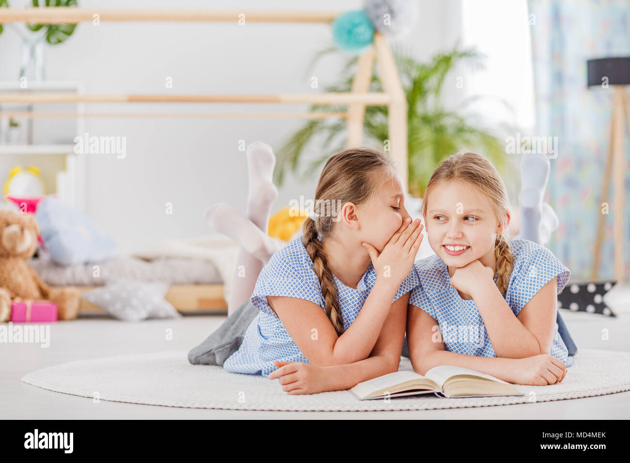 Mischievous twin sisters whispering secrets, lying on a white rug in a cozy children's bedroom - Stock Image