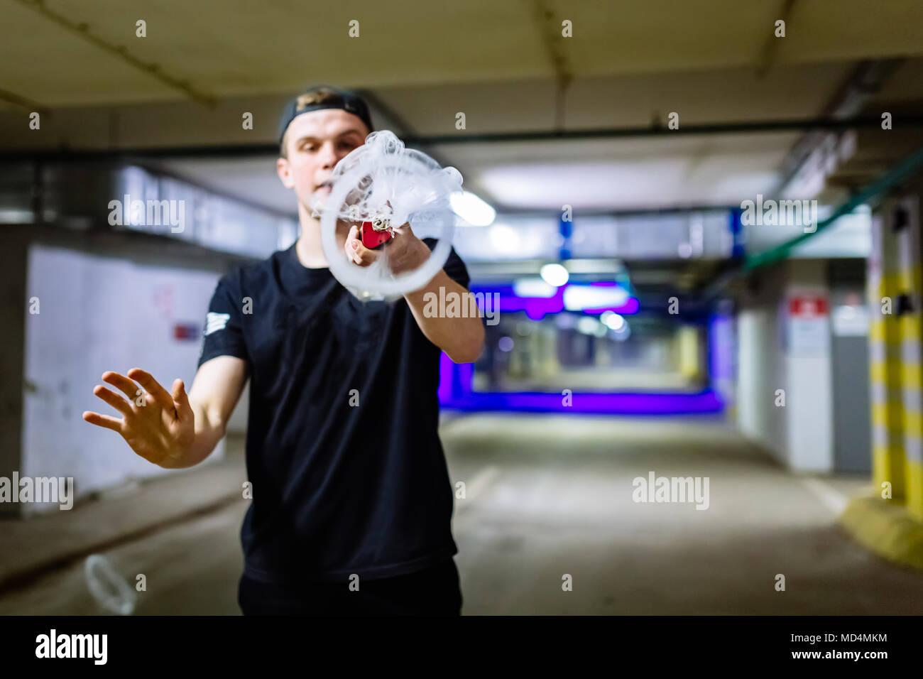 Man in cap smoke an electronic cigarette performing various kind of vaping tricks - Stock Image