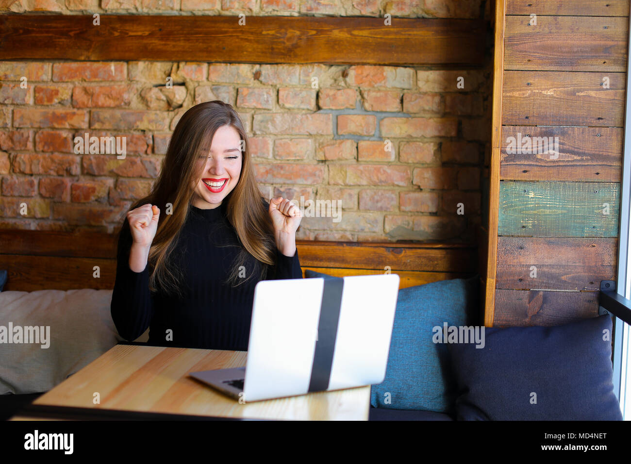 Lucky girl with make up rejoicing with laptop at cafe. - Stock Image