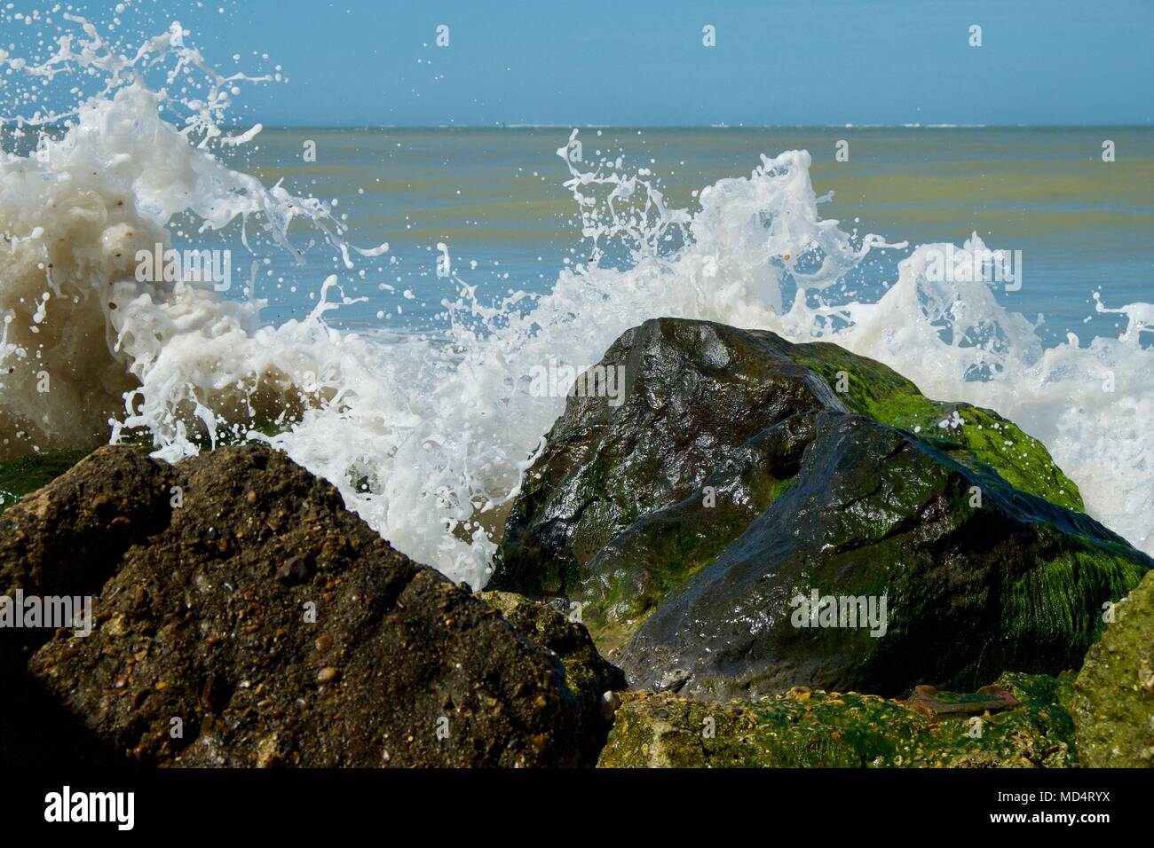 spume and wave on rocks at Colwell Bay, Isle of Wight, United Kingdom - Stock Image