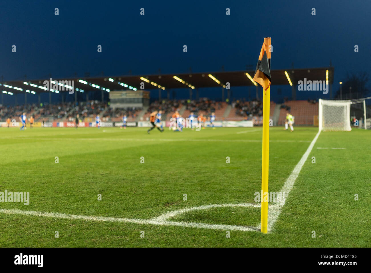 Corner flag at the football pitch, in the background players in action. - Stock Image