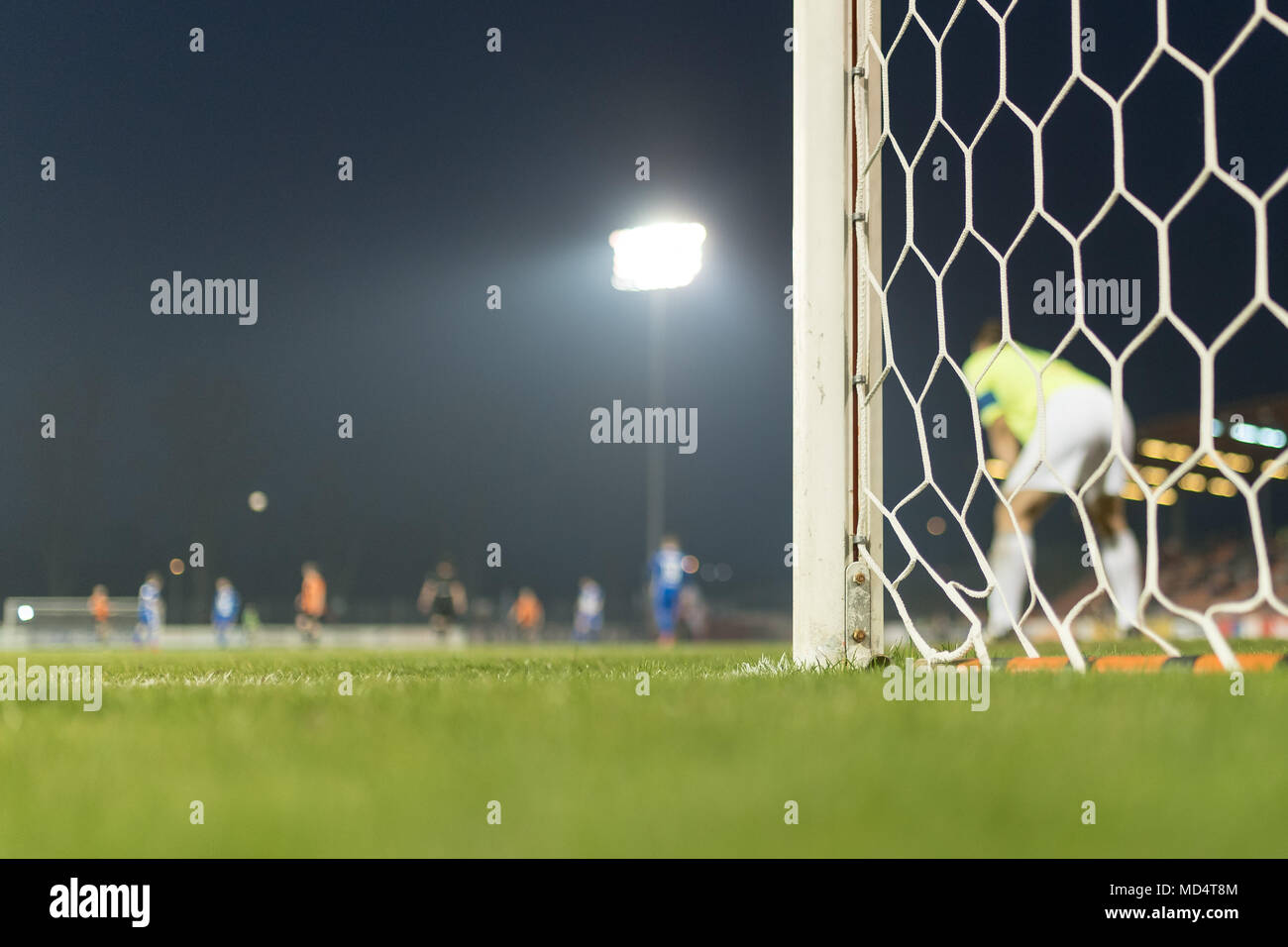 Detail of the post and net of the football goal in the background players in action. - Stock Image