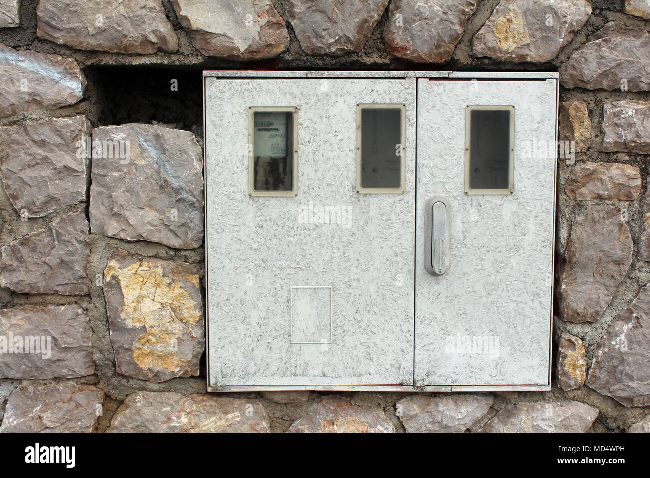 Electric meter box mounted on stone wall with one out of three meters inside and working - Stock Image