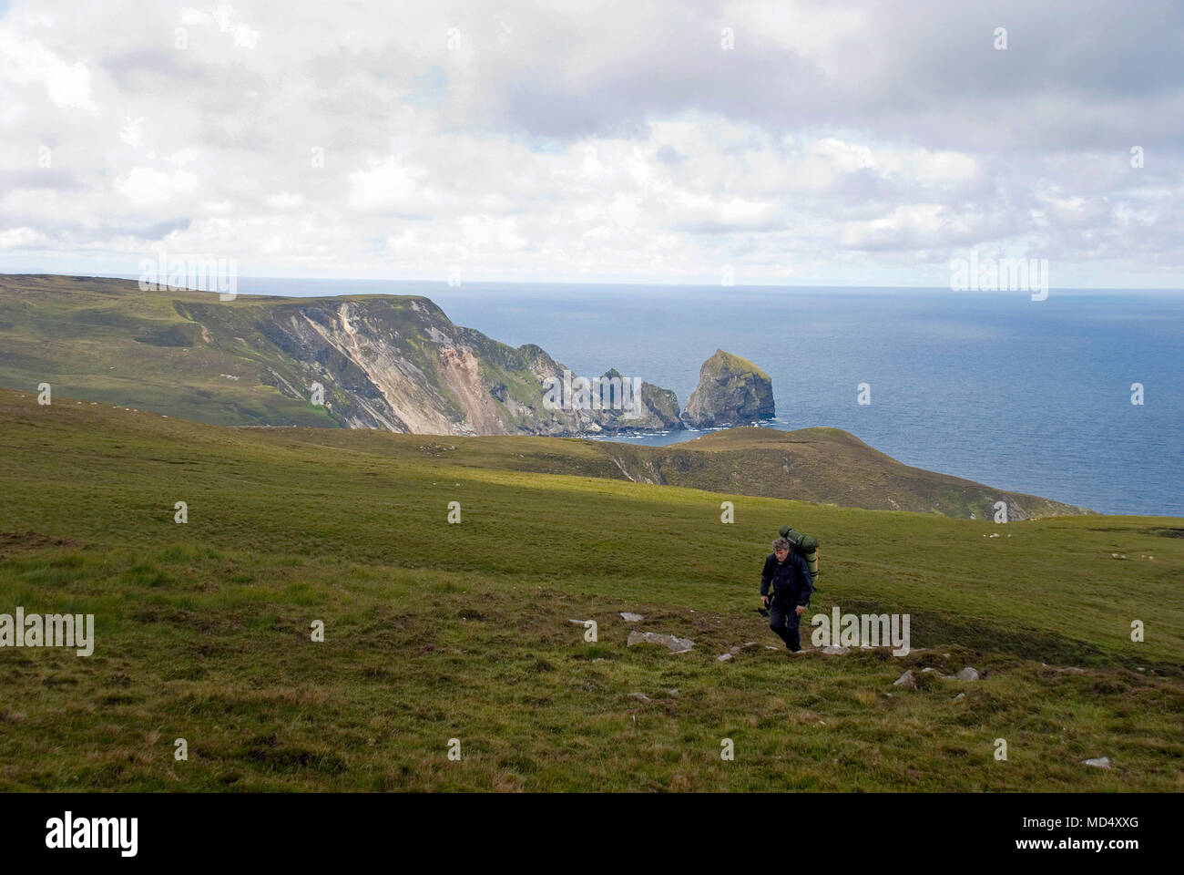 Hill walker crossing Slieve Tooey mountain from Port in County Donegal, Ireland. - Stock Image