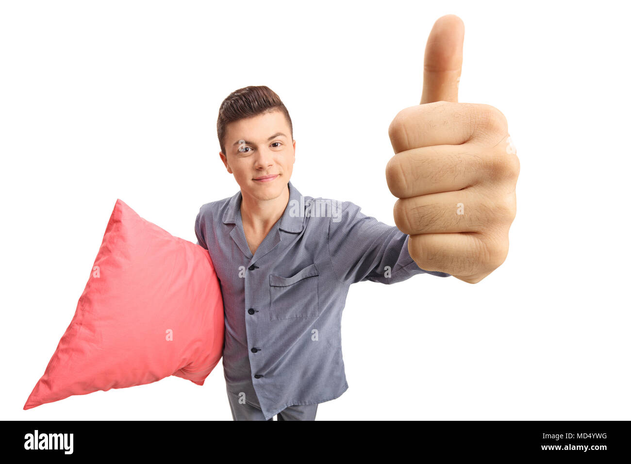 Teenage boy in pajamas holding a pillow and making a thumb up gesture isolated on white background - Stock Image