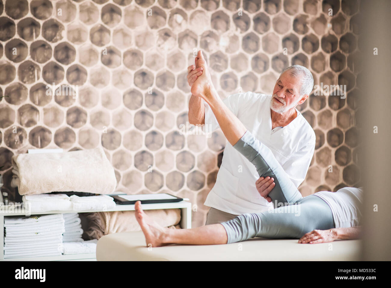 Senior physiotherapist working with a female patient. - Stock Image