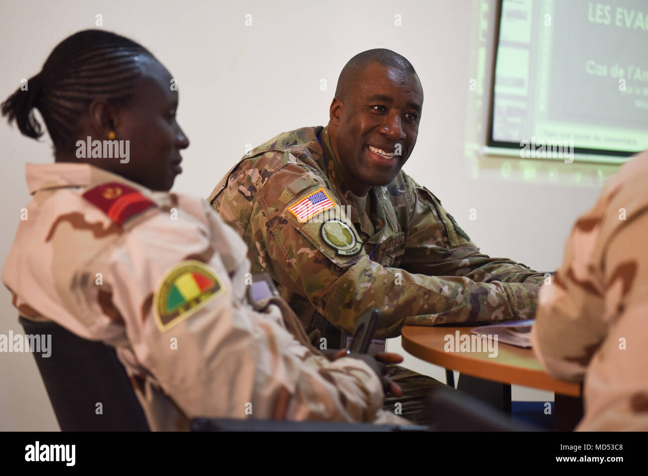 Capt. Malick Traore, 818th Mobility Support Advisory Squadron aeromedical evacuation project manager, discusses principles of altitude physiology and stresses of flight with a Malian chief of medical operation during African Partnership Flight Senegal, March 20, 2018. Partnership flights are U.S. Air Forces Africa's premier security cooperation program with African partner nations to improve professional military aviation knowledge and skills. (U.S. Air Force photo by Capt. Kay Magdalena Nissen) - Stock Image
