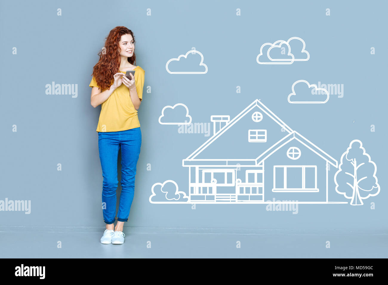 Pretty woman holding a smartphone and planning buying a house - Stock Image