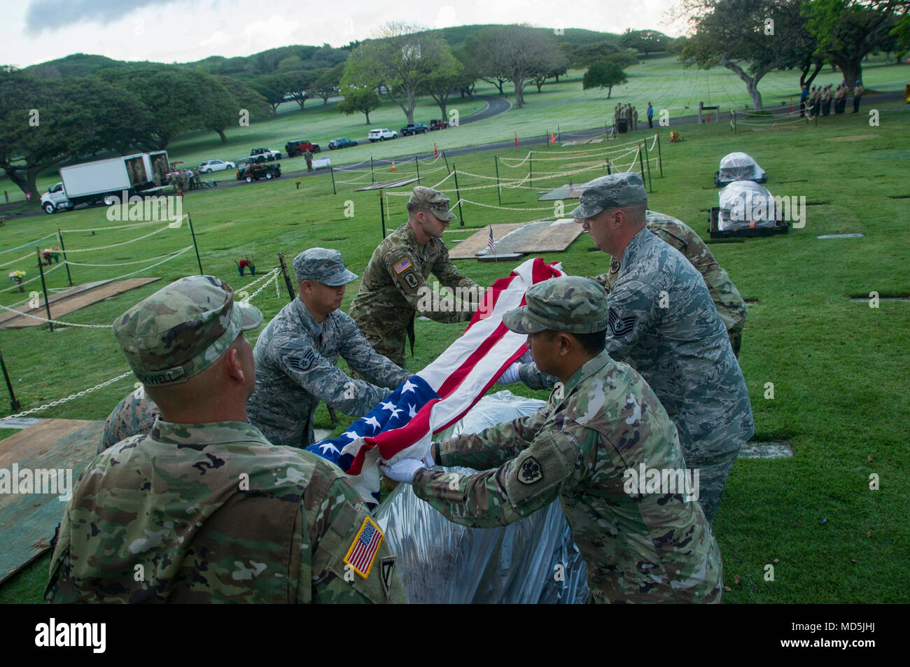 Members of the Defense POW/MIA Accounting Agency (DPAA) drape the colors on to a casket during a disinterment ceremony at the National Memorial Cemetery of the Pacific, Honolulu, Hawaii, March 26, 2018. The remains will be transferred to the DPAA laboratory for analysis and identification. DPAA's mission is to provide the fullest possible accounting of our missing personnel to their families and the nation. (U.S. Air Force photo by Senior Airman Apryl Hall) - Stock Image