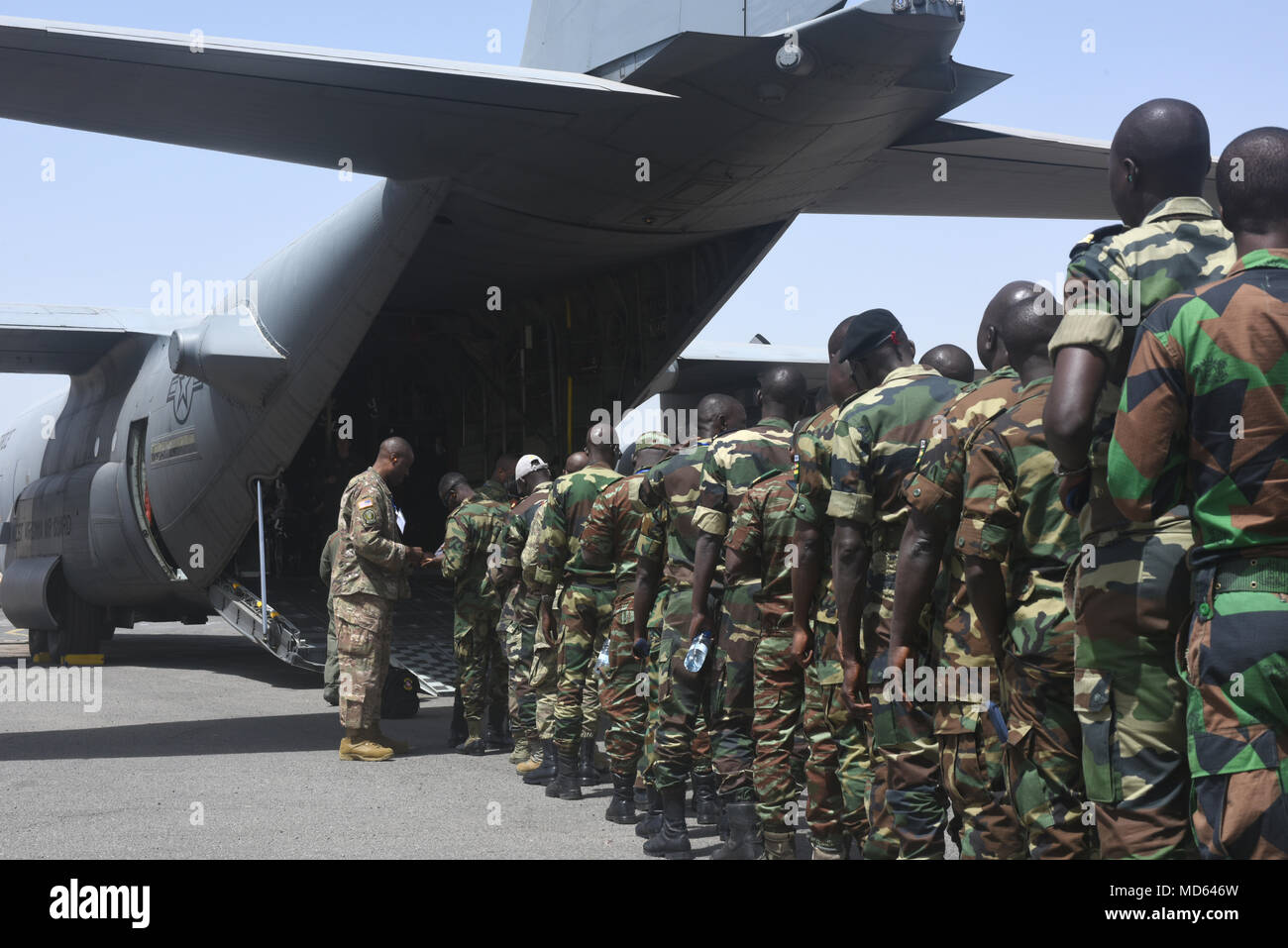 Participants of African Partnership Flight Senegal prepare to board a C-130H Hercules, assigned to the 130th Airlift Wing, West Virginia Air National Guard, at Captain Andalla Cissé Air Base, Senegal, March 22, 2018. The APF program is U.S. Air Forces in Africa's premier security cooperation program with African partner nations to improve professional military aviation knowledge and skills. (U.S. Air Force photo by Airman 1st Class Eli Chevalier) - Stock Image