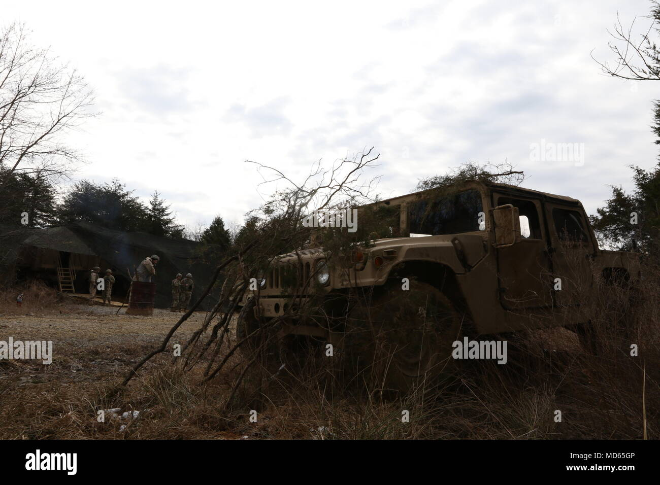 A HUMVEE is concealed in front of the 364th Expeditionary Sustainment Command's Jump Tactical Operations Center Coyote in Fort Knox, Ky., March 22, 2018, during Combined Situational Training Exercise - Bridge. The jump TOC demonstrated the 364th ESC's capability to perform sustainment operations from a mobile environment. - Stock Image