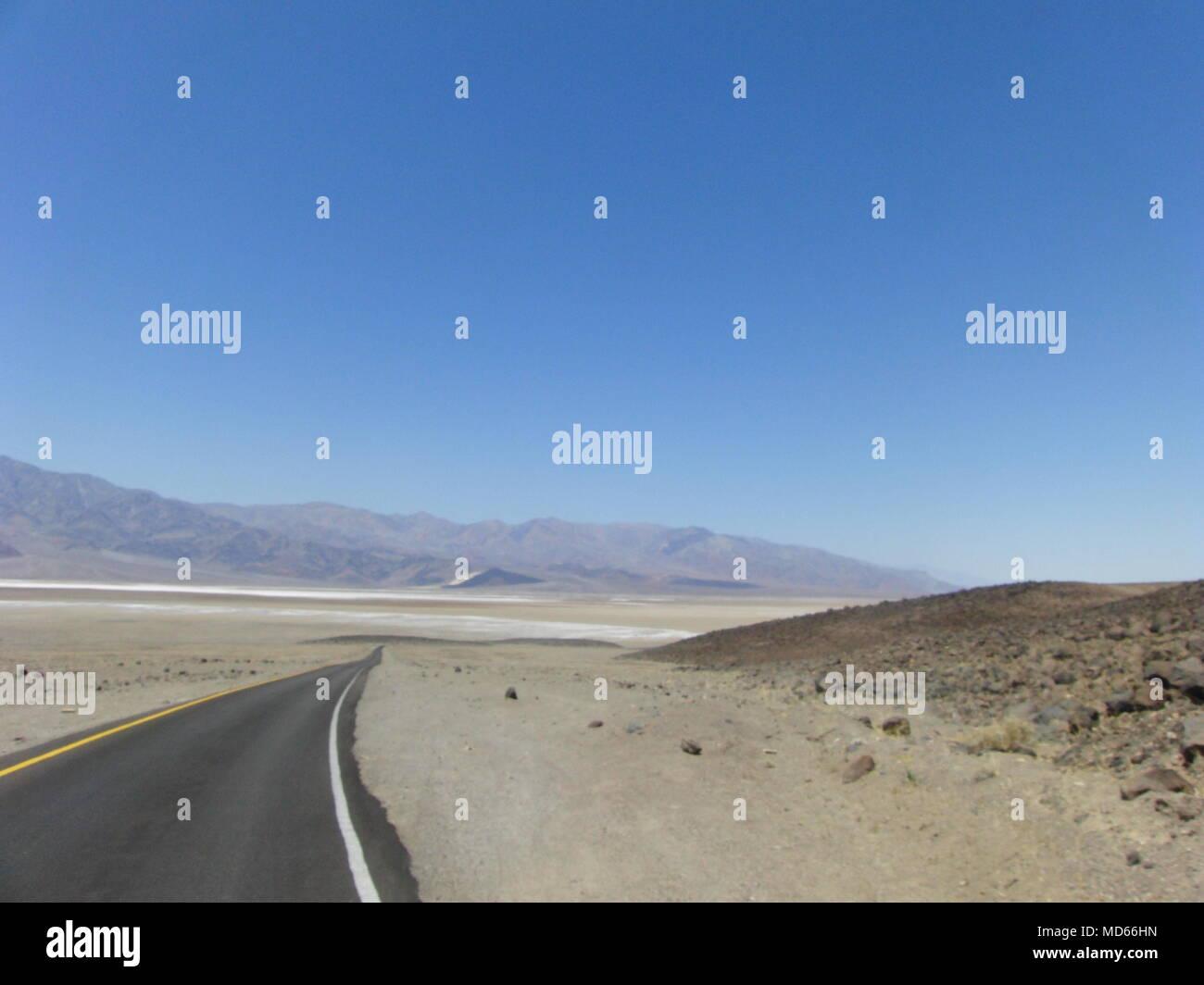 Desert road. Abrupt turn. Mountain landscape. Blue sky. - Stock Image
