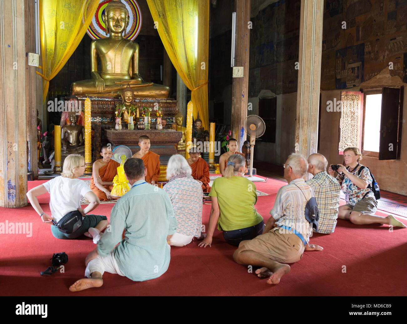 Cambodia tourists - Western tourists getting a blessing from Buddhist monks in a temple, Siem Reap, Cambodia Asia - Stock Image