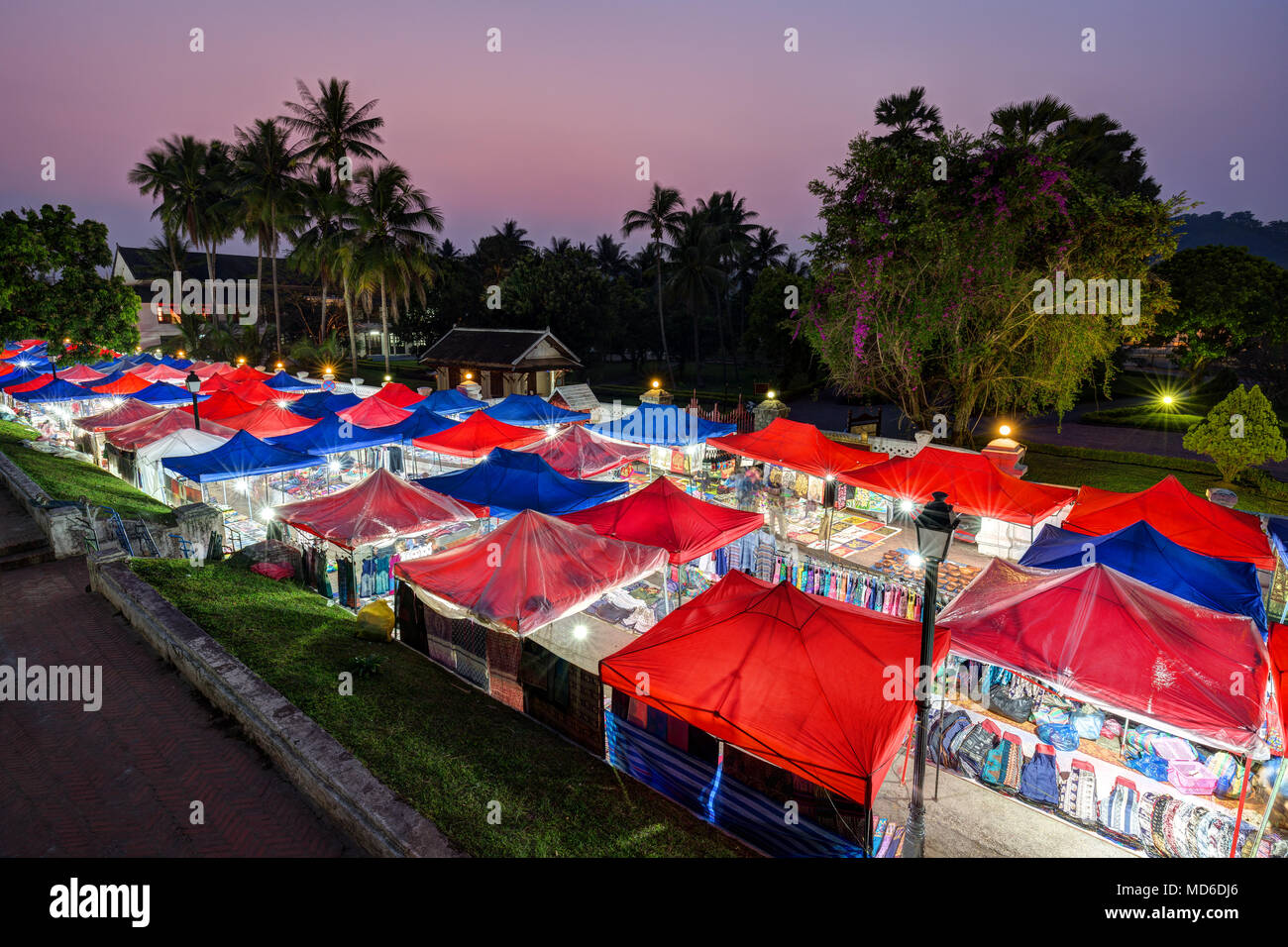 Many lit market stalls at the night market in Luang Prabang, Laos, viewed from above at dusk. - Stock Image
