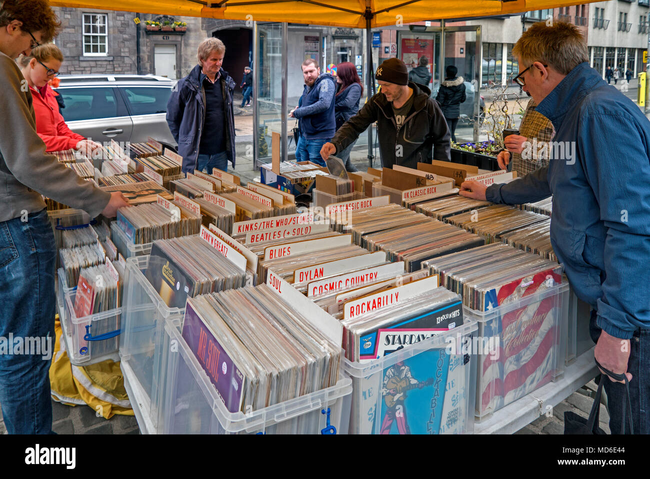 Customers browsing through vinyl records on a stall in the