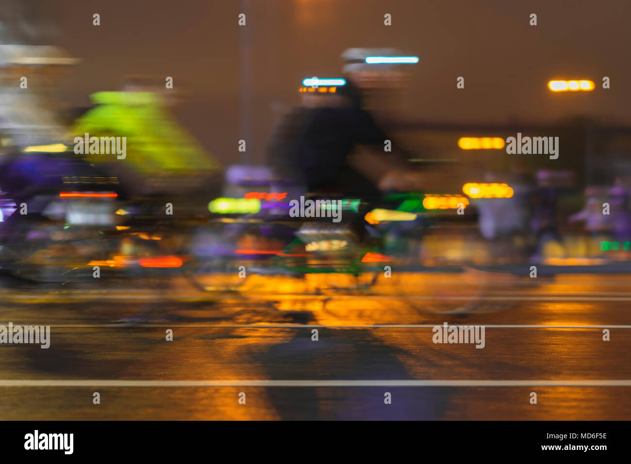 Motion blurred image of riding cyclists. Parade of bicyclists in city, night, abstract. Modern active lifestyle, healthy lifestyle concept - Stock Image