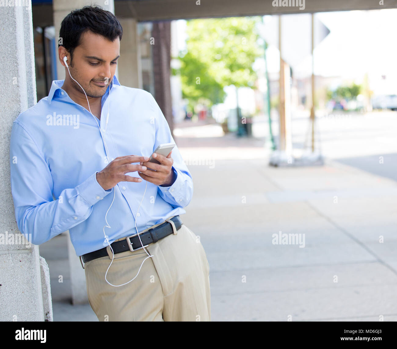 Closeup portrait, young happy business man standing, checking his cellphone, listening to music, isolated on background of a city road with trees on a - Stock Image