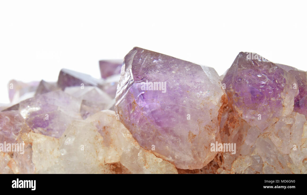 Close-up of an amethyst crystal on white background - Stock Image