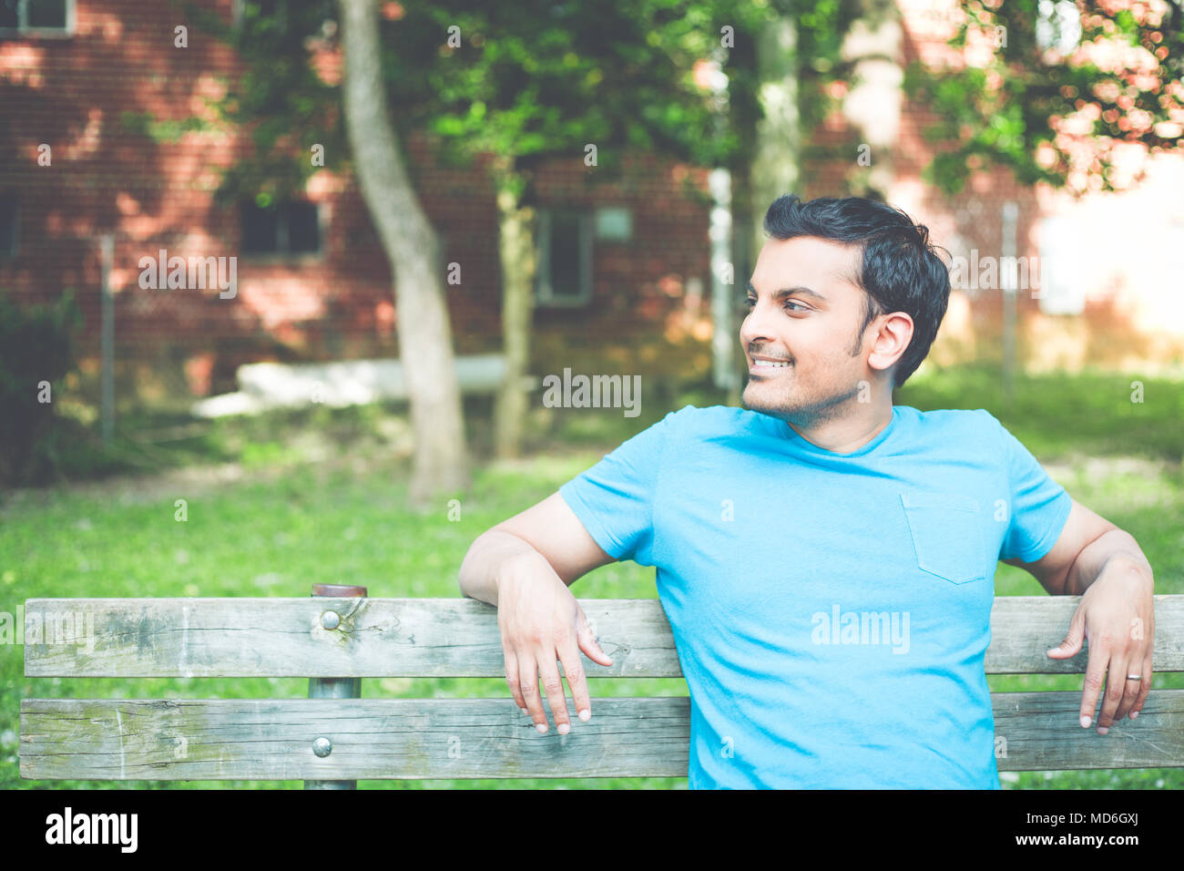 Closeup portrait, happy smiling, regular young man in blue shirt sitting on wooden bench, relaxed looking to side, isolate background trees, woods. Re - Stock Image