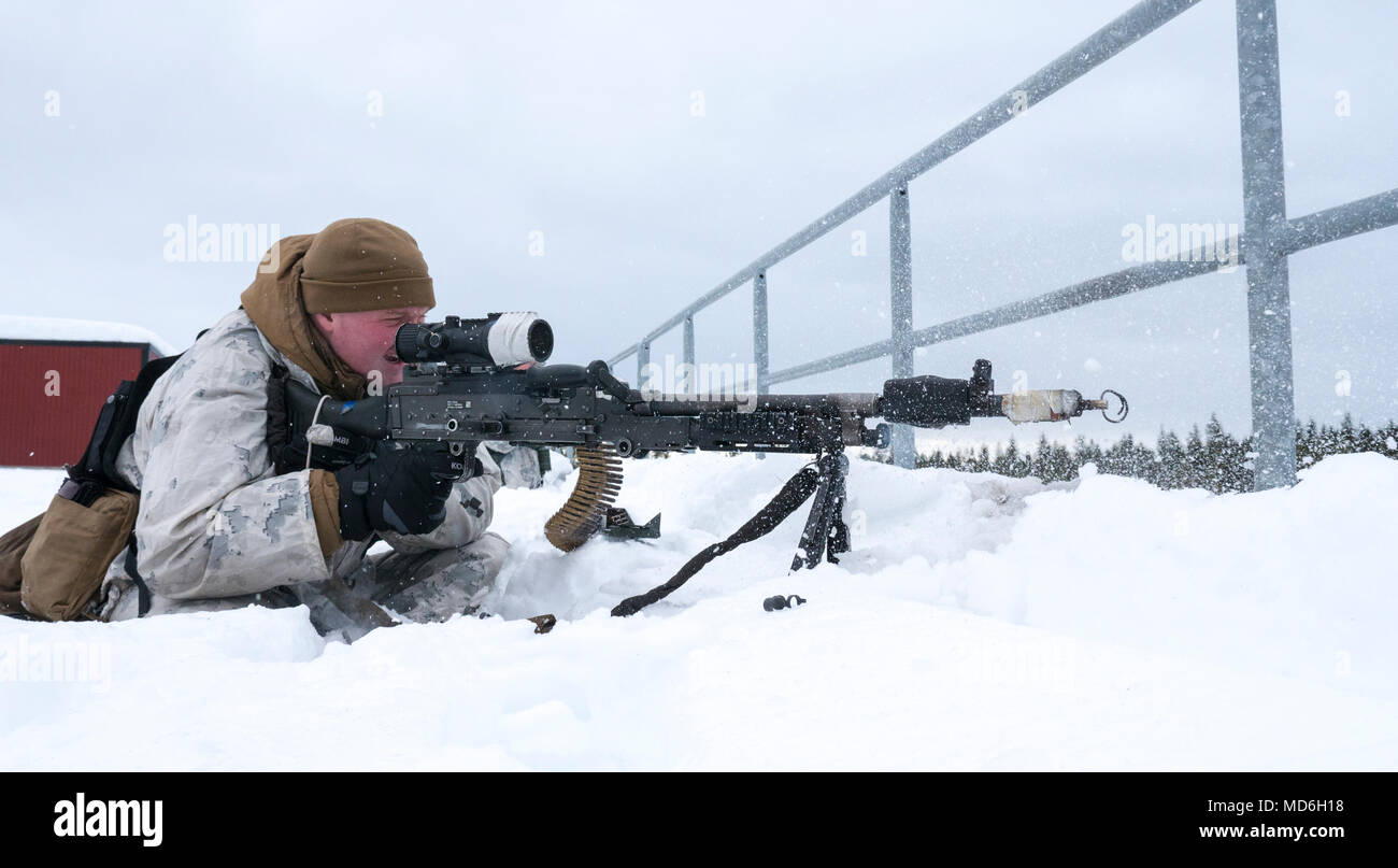 Marine with Marine Rotational Force-Europe shoots at the opposing force while conducting Military Operations Urbanized Terrain (MOUT) training during Exercise Winter Sun 18 in Boden, Sweden, March 19, 2018. Winter Sun 18 is a multinational exercise that integrates dismounted elements with a mechanized infantry and enhances strategic cooperation between the U.S. Marines and Swedish forces in a cold-weather environment. (U.S. Marine Corps photo by Cpl. Raul Torres/Released) - Stock Image