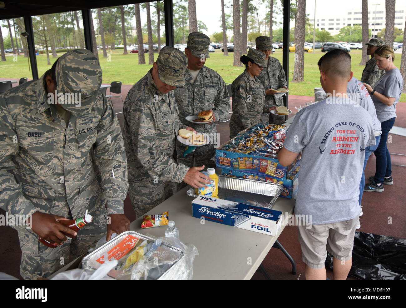 Keesler personnel get food during the Air Force Assistance Fund burger burn at the Crotwell Track March 26, 2018, on Keesler Air Force Base, Mississippi. The AFAF is an annual effort to raise funds for the charitable affiliates that provide support to our Air Force family in need. (U.S. Air Force photo by Kemberly Groue) - Stock Image