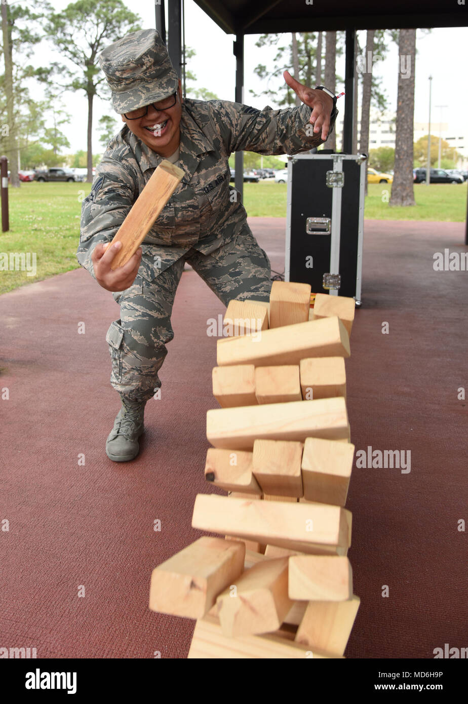 U.S. Air Force Senior Airman Lucerno Salazar-Escamilla, 81st Surgical Operations Squadron physical medicine administration, participates in a game of Jenga during the Air Force Assistance Fund burger burn at the Crotwell Track March 26, 2018, on Keesler Air Force Base, Mississippi. The AFAF is an annual effort to raise funds for charitable affiliates that provide support to our Air Force family in need. (U.S. Air Force photo by Kemberly Groue) - Stock Image