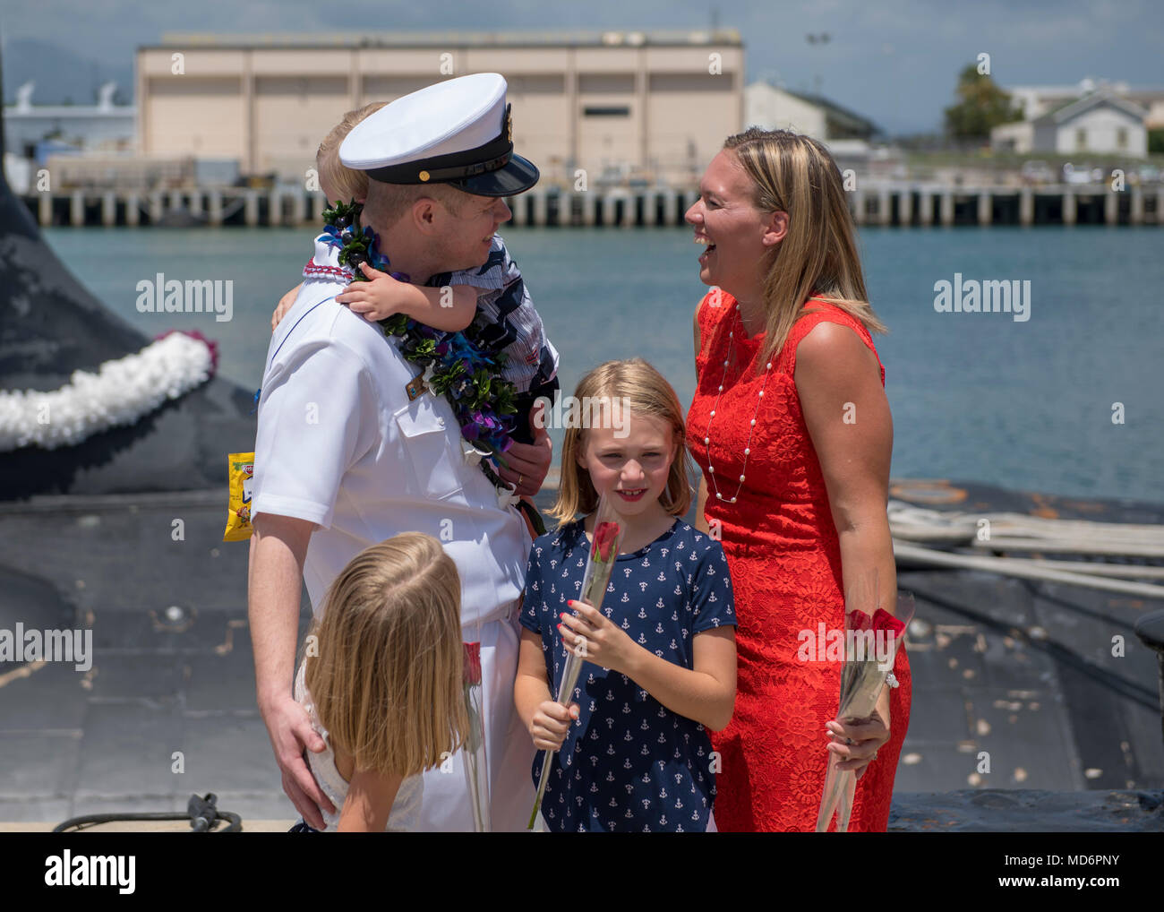 180330-N-LY160-0182 PEARL HARBOR, Hawaii (March 30, 2018) Chief Electronics Technician Nuclear Christopher Fendley, assigned to the Virginia-class fast-attack submarine USS Mississippi (SSN 782), greets his family during a homecoming ceremony in Joint Base Pearl Harbor-Hickam, March 30. Mississippi successfully completed a six-month Western Pacific deployment. (U.S. Navy photo by Mass Communication Specialist 2nd Class Michael H. Lee/ Released) - Stock Image