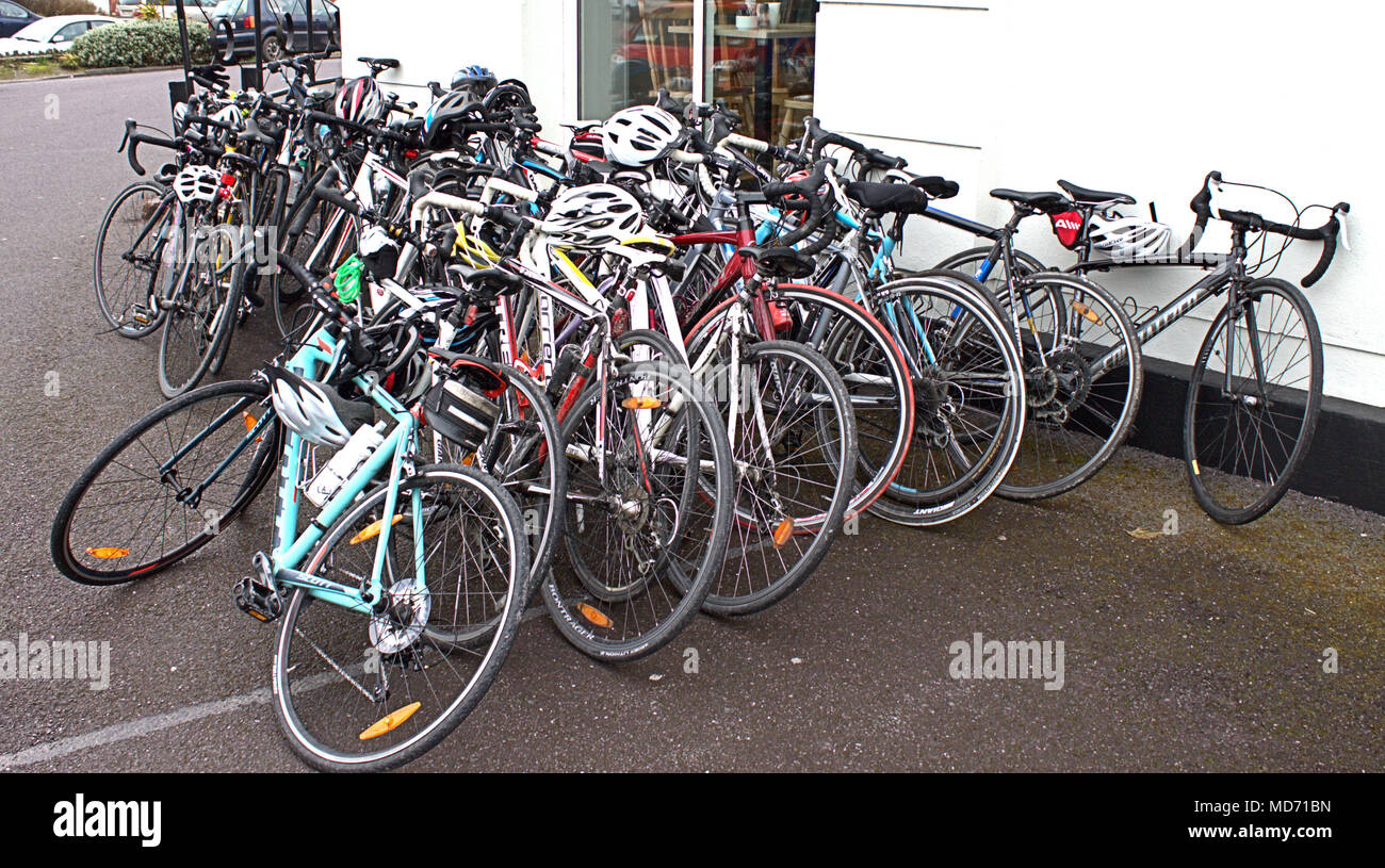 bicycles stacked against a cafe wall in skibbereen, ireland prior to being used for a charity bike ride by female students. - Stock Image