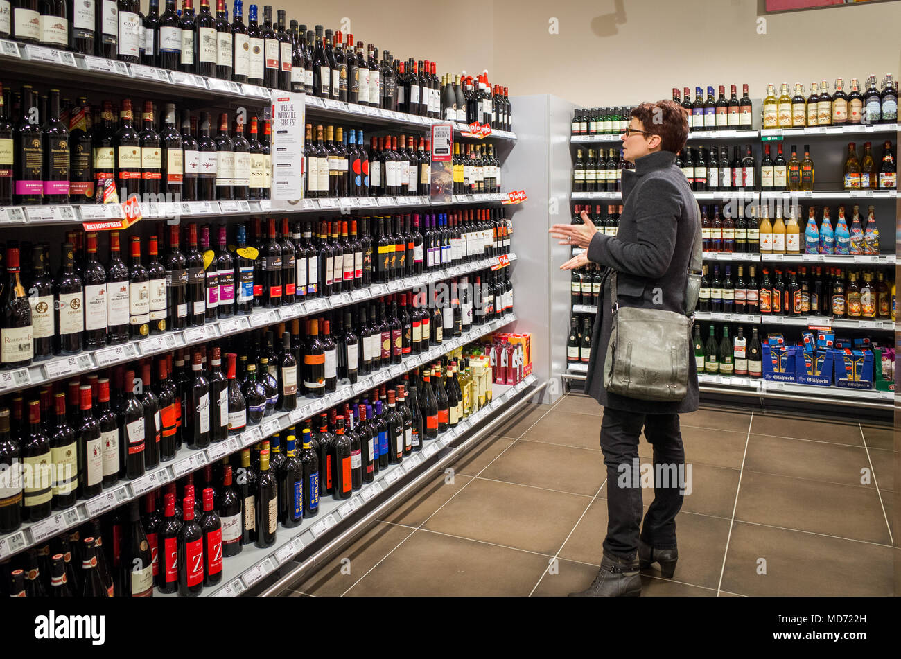 Woman choosing bottle of wine in German supermarket - Stock Image