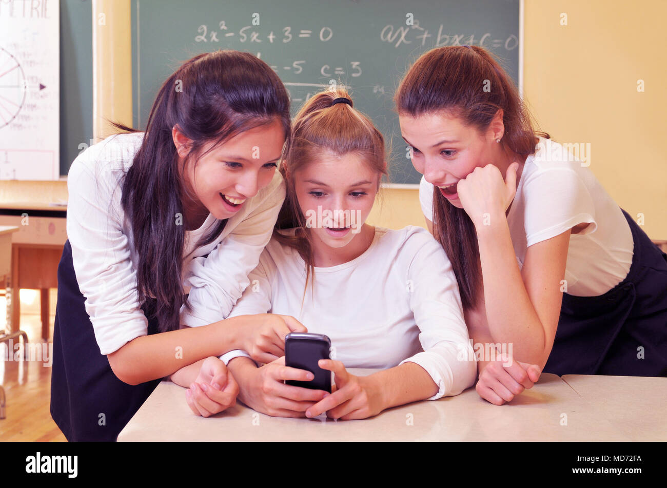 Three happy school girls in their math class - Stock Image