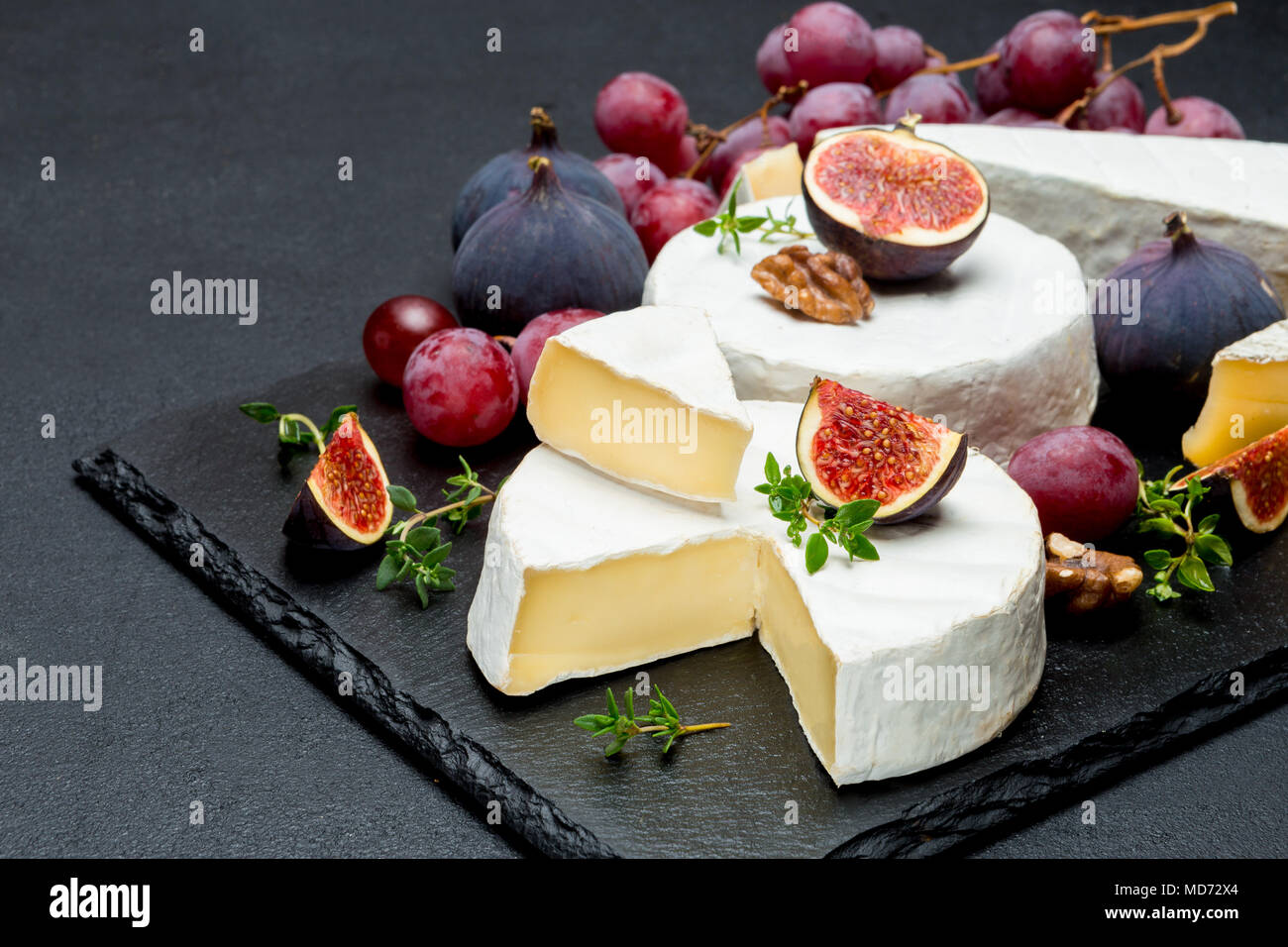 Camembert cheese and cut a slice on stone serving board - Stock Image