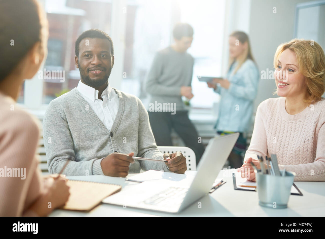 Multi-ethnic team of talented designers gathered together at spacious open plan office and brainstorming on ambitious joint project - Stock Image