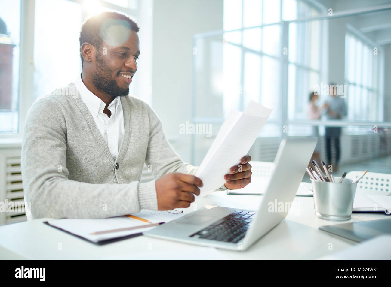 Waist-up portrait of cheerful African American businessman studying document while sitting at desk of modern open plan office, lens flare - Stock Image