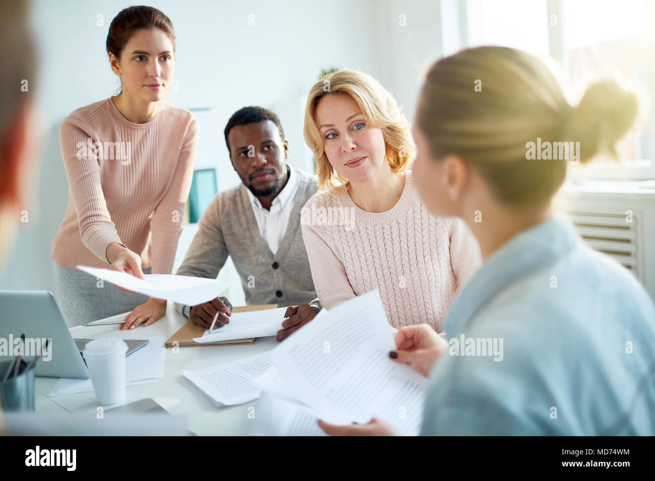 Attractive young manager passing document to fair-haired colleague while having working meeting at spacious open plan office - Stock Image
