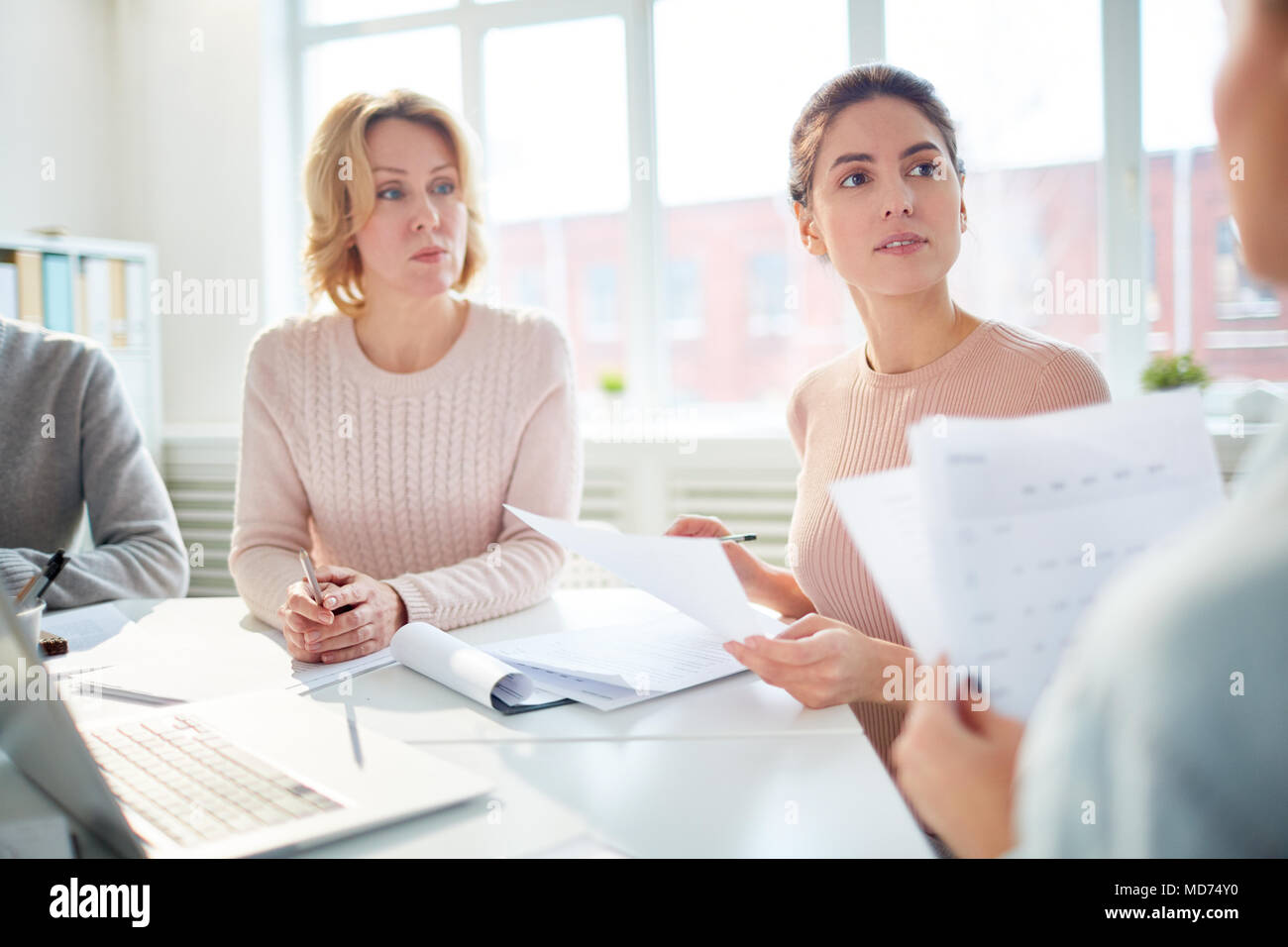 Working meeting at spacious open plan office: group of financial managers analyzing statistic data while sitting at table - Stock Image