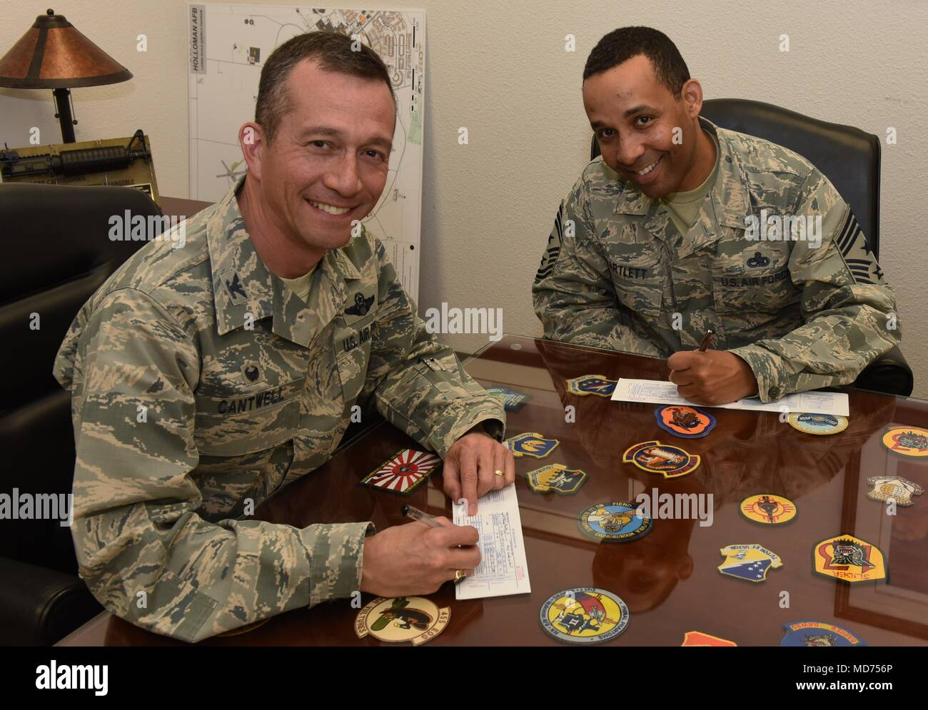 Col. Houston Cantwell, 49th Wing commander, and Chief Master Sgt. Barrington Bartlett, 49th Wing command chief, sign up to make a donation to the Air Force Assistance Fund at Holloman Air Force Base, N.M., March 26, 2018. The four charities that are involved in AFAF are the Air Force Aid Society, General and Mrs. Curtis E. LeMay Foundation, the Air Force Villages, and the Air Force Enlisted Village. (U.S. Air Force photo by Staff Sgt. Timothy Young) - Stock Image