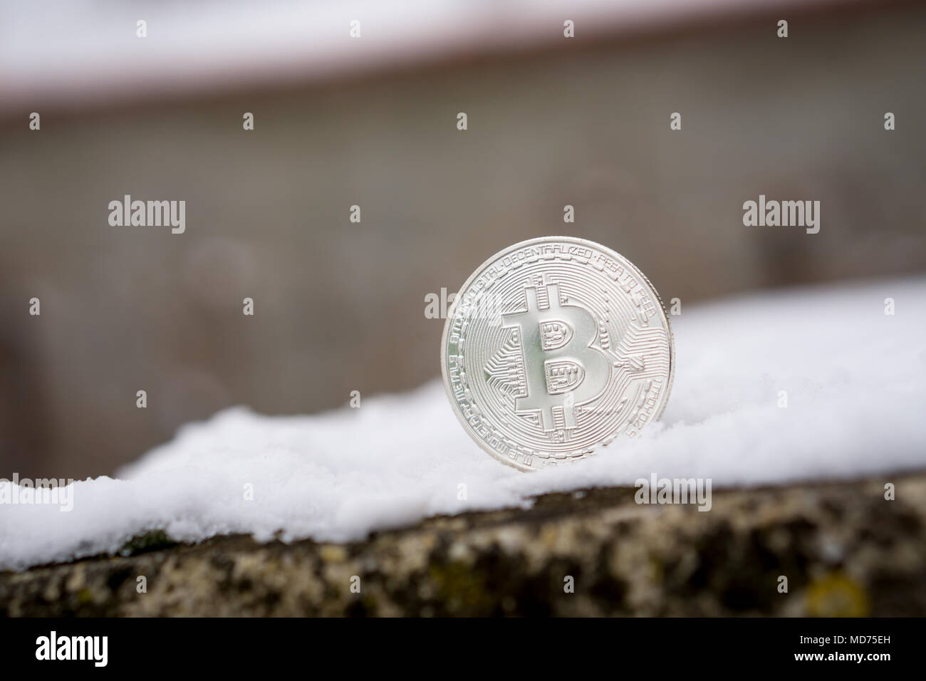 A silver Bitcoin placed in snow on concrete. Isolated scene of  cryptocurrency in snow - Stock Image