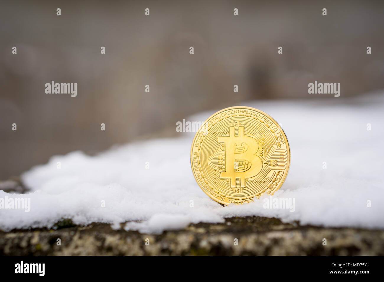 A gold Bitcoin placed in snow on concrete. Isolated scene of  cryptocurrency in snow - Stock Image