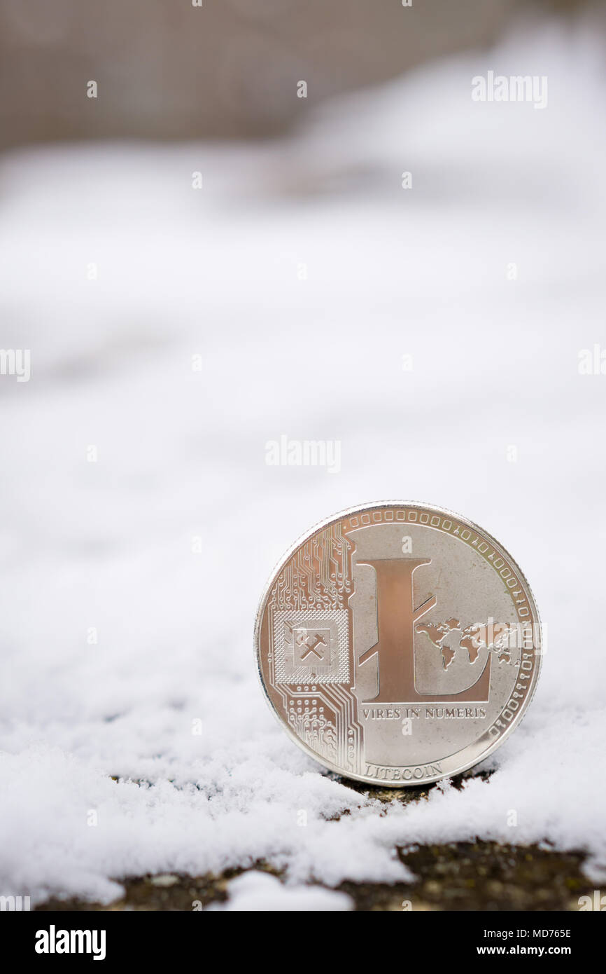 A silver litecoin placed in snow on concrete. Isolated scene of  cryptocurrency in snow - Stock Image